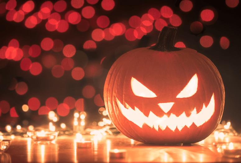 Photo of a Halloween pumpkin surrounded by candles